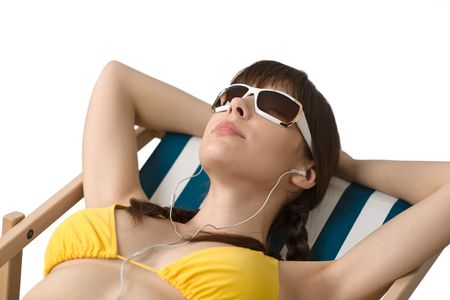 Beach - Woman with ear buds and sunglasses relax in bikini, listen to music photo