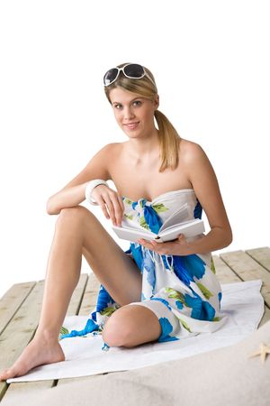 Beach - woman sitting on wooden deck with book, sunbathing, wearing pareo photo