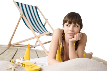 Beach - Attractive woman in bikini sunbathing, deck chair in background photo