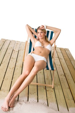 Beach - Woman in white bikini sunbathing on deck chair with sand photo