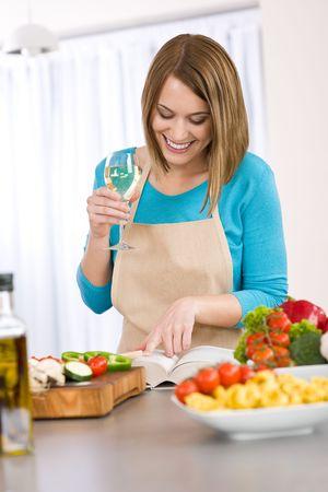 ama de casa: Cocina - Smiling mujer receta de lectura de libros de cocina, pastas italianas y vegetales Foto de archivo