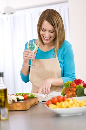 aprons: Cooking - Smiling woman reading recipe from cookbook, Italian pasta and vegetable Stock Photo