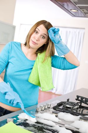 stove: Cleaning - Tired woman cleaning stove in modern kitchen with brush Stock Photo
