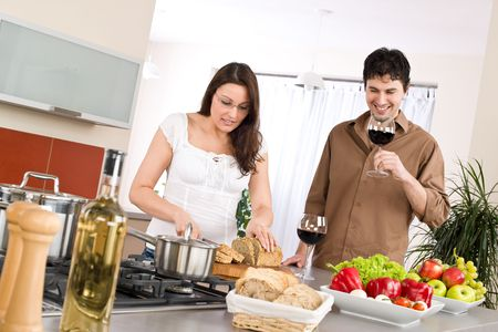 Cooking - happy couple together in modern kitchen drink red wine and cut bread Stock Photo - 6796267