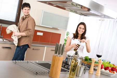Young couple cook in modern kitchen, man helping with dishes Stock Photo - 6796269