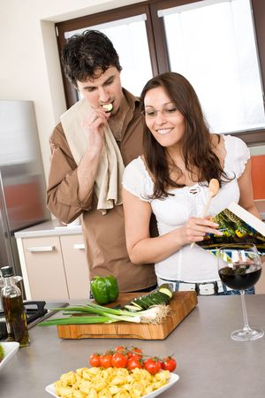 Smiling couple in modern kitchen cook together with cookbook Stock Photo - 6796261