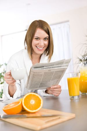 news stand: Breakfast - Smiling woman reading newspaper in kitchen, with coffee and fresh orange juice Stock Photo