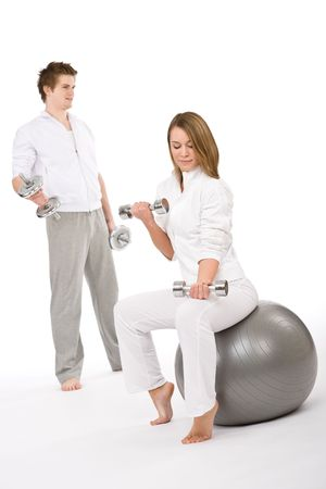 Fitness - Young couple exercise with weights and ball on white background photo