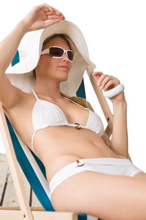 Beach - woman in bikini with hat and sunglasses sunbathing lying down on deck chair photo
