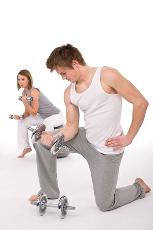 Fitness - Young healthy couple exercise with metal weights on white background photo