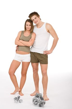 Fitness - Young healthy couple with weights in sportive outfit on white background photo