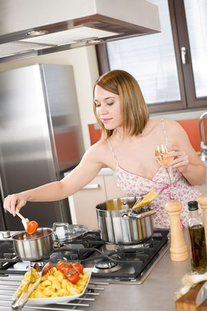 Attractive woman cooking spaghetti and tomato sauce in modern kitchen photo