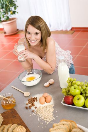 Baking - Happy woman prepare healthy ingredients for organic cake dough photo