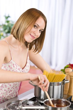 Cooking - Young woman tasting Italian tomato sauce in modern kitchen, preparing spaghetti photo