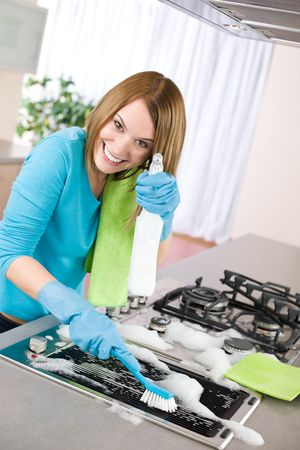 wiping: Young woman cleaning stove in modern kitchen with brush and glove Stock Photo