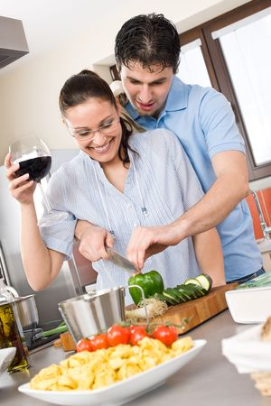 Happy couple cut vegetables in kitchen, cook together photo