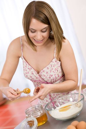 Baking - Happy woman tasting healthy ingredient for organic bread dough, with honey Stock Photo - 6801828