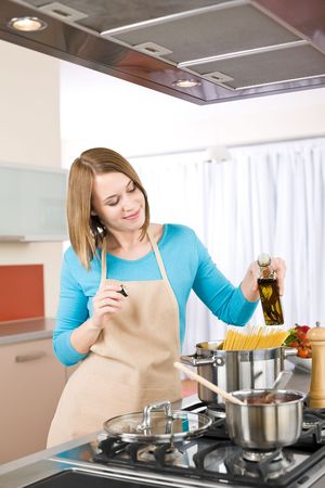 Cooking - Young woman with spaghetti on stove cooking Italian cousine photo