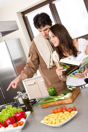 Smiling couple in modern kitchen cook together with cookbook Stock Photo - 6801832