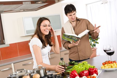 Happy couple cook together in modern kitchen with cookbook photo