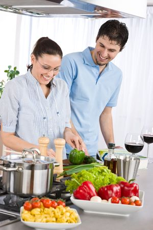 cookbook: Smiling couple drink red wine cooking in kitchen with vegetables
