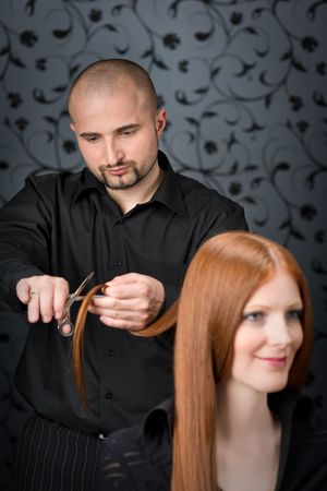 Professional hairdresser with long red hair fashion model at luxury salon, hair cut with scissors photo
