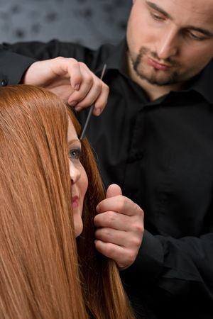 comb hair: Professional hairdresser with long red hair fashion model at luxury salon, comb hair