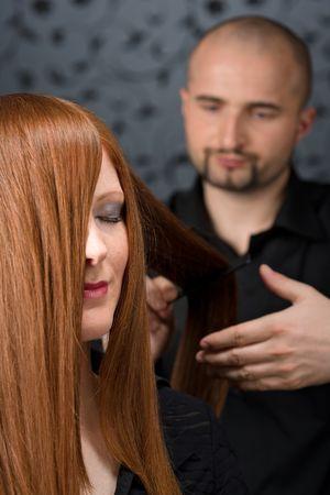 comb hair: Parrucchiere professionali con i capelli lunghi rossi modella nel salone di lusso, pettine capelli
