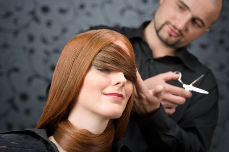 Professional hairdresser with long red hair fashion model at luxury salon, hair cut with scissors