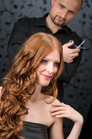 Professional hairdresser with long red curly hair fashion model at black luxury salon, hair cut with scissors photo