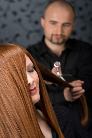 Professional hairdresser with long red hair fashion model at luxury salon, hair cut with scissors Stock Photo - 6869885