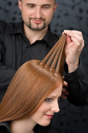hair design salon: Professional hairdresser with long red hair fashion model at black luxury salon Stock Photo