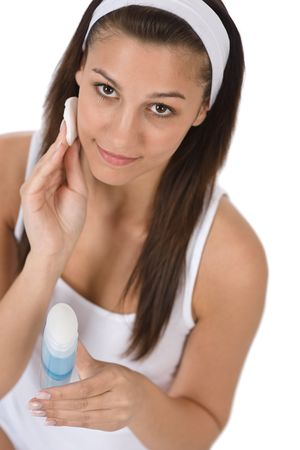 Beauty facial care - Teenager woman cleaning acne skin with cotton pad on white background Stock Photo - 6839717