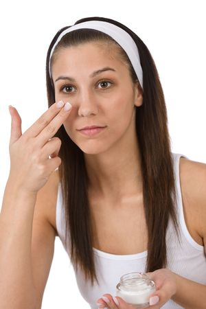 Beauty facial care - Young woman apply moisturizer on white background Stock Photo - 6839690
