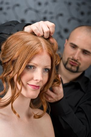 Professional hairdresser with long red curly hair fashion model at luxury salon photo