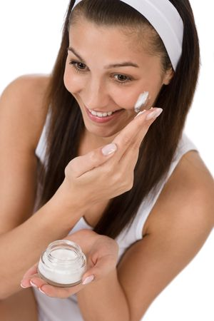 Beauty facial care - Young woman apply moisturizer on white background Stock Photo - 6839714