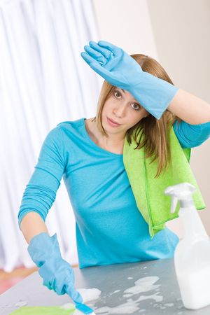 Tired woman cleaning kitchen with brush and gloves photo