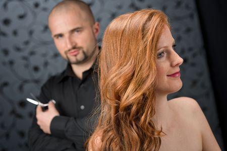 Peluquer�a profesional con modelo de moda de pelo rizado largo rojo en Sal�n de lujo negro, pelo cortado con tijeras. Foto de archivo - 6868348