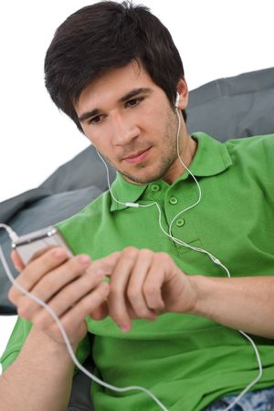 Young man with ear buds listening to music, holding mp3 player Stock Photo - 6839795