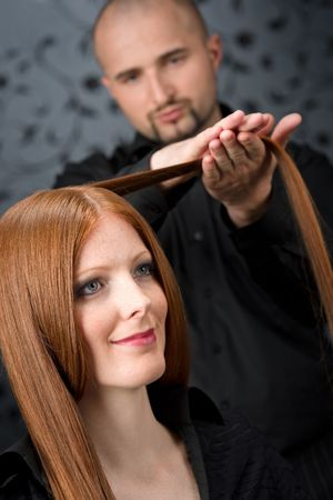 Professional hairdresser with long red hair fashion model at black luxury salon photo