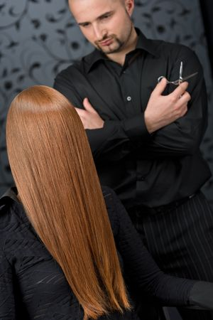 stylists: Professional hairdresser with long red hair fashion model at luxury salon, hair cut with scissors