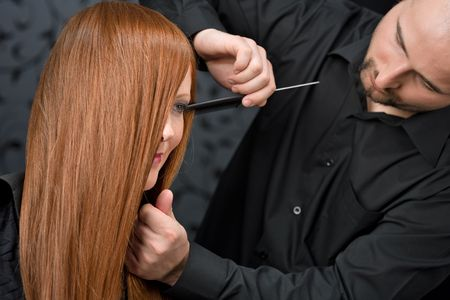Professional hairdresser with long red hair fashion model at luxury salon, comb hair photo