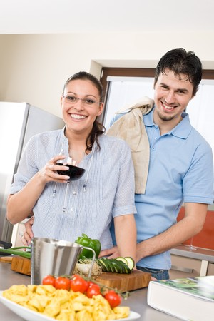 Cheerful couple in modern kitchen cook together, drink red wine photo
