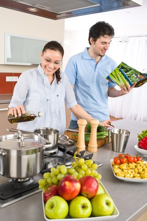 Young happy couple cook in kitchen with cookbook, pasta, vegetable photo