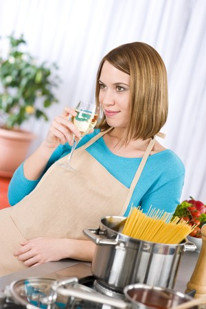 Cooking - Young woman with spaghetti on stove cooking Italian cousine and glass of white wine photo