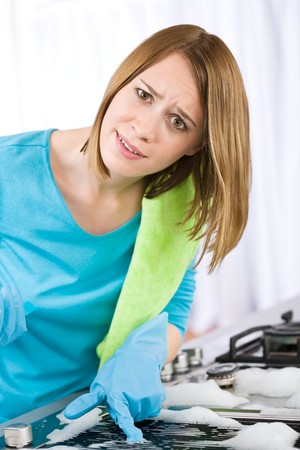 Young woman cleaning stove in modern kitchen with brush and glove photo