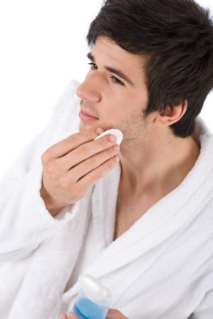 pulizia viso: Cura del viso - giovane pulizia viso con lozione su sfondo bianco