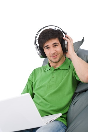 Young man with laptop and headphones sitting on bean bag on white background Stock Photo - 6914637