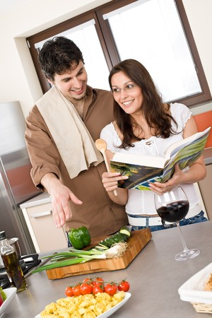 Smiling couple in modern kitchen cook together with cookbook photo