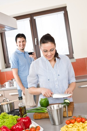 Happy couple cook in modern kitchen, woman cutting vegetable photo